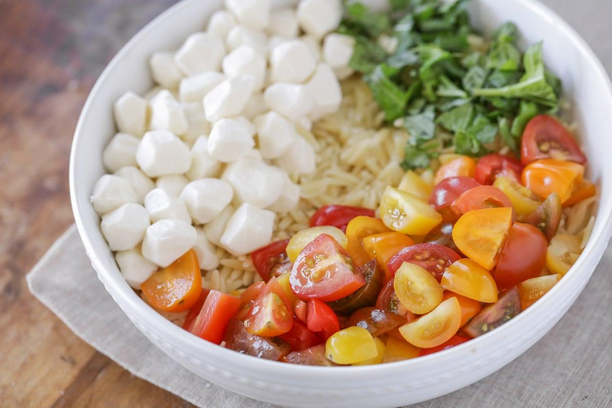 White bowl filled with orzo pasta, fresh mozzarella, tomoatoes and basil