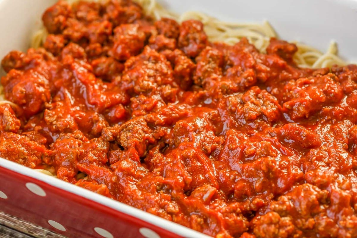 Cheesy Baked Spaghetti with meat sauce in casserole dish before baking