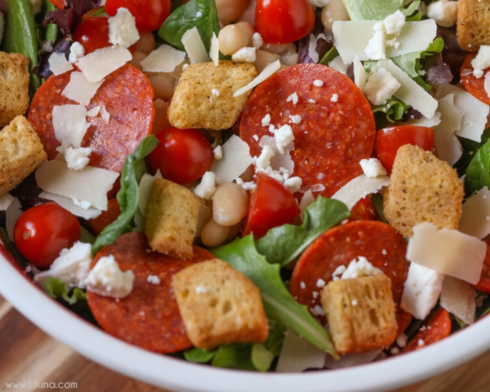 Pizza Salad - filled with cannellini beans, pepperoni, tomatoes, Feta and Parmesan cheese and topped with a homemade Herb Dressing!