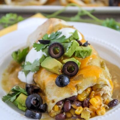 green chili smothered burrito with olives, cilantro and avocado on plate
