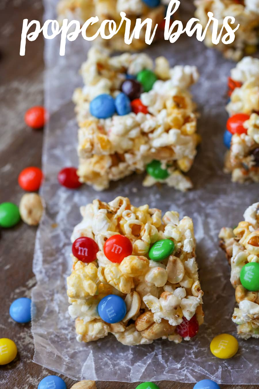 Popcorn Bars - Delicious bars made from popcorn, marshmallows, peanuts and M&Ms. Everybody loves this yummy treat!