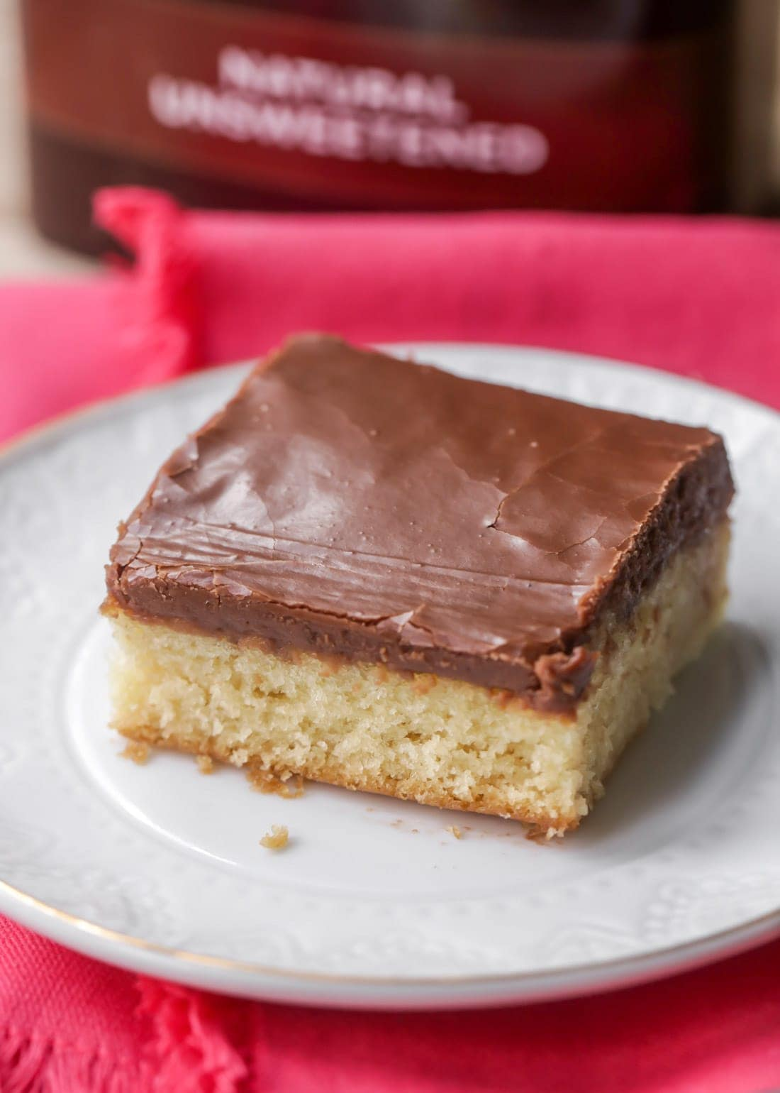 A slice of white Texas sheet cake with chocolate fudge frosting on a plate
