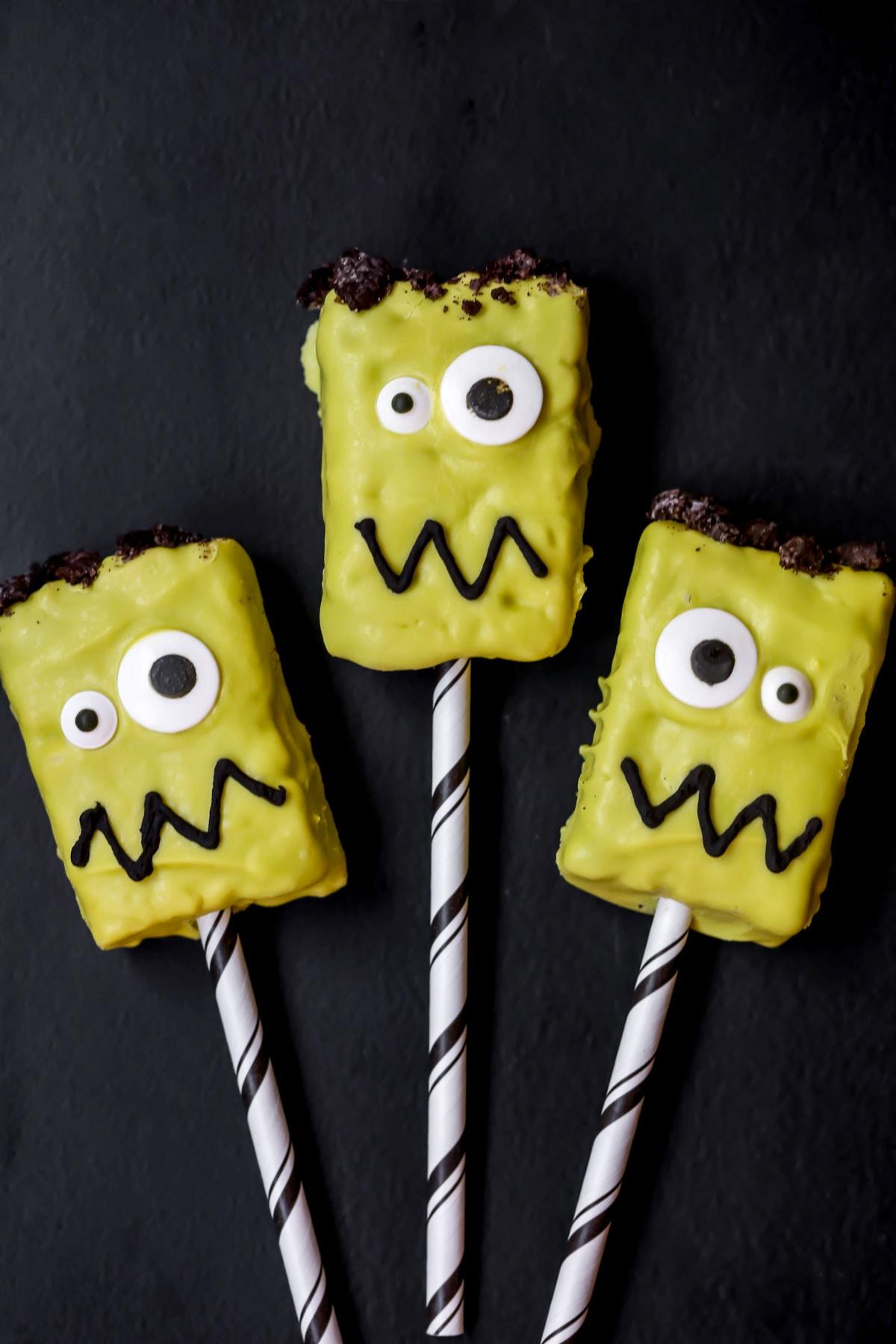 Frankenstein Rice Krispies Treats on black and white straws