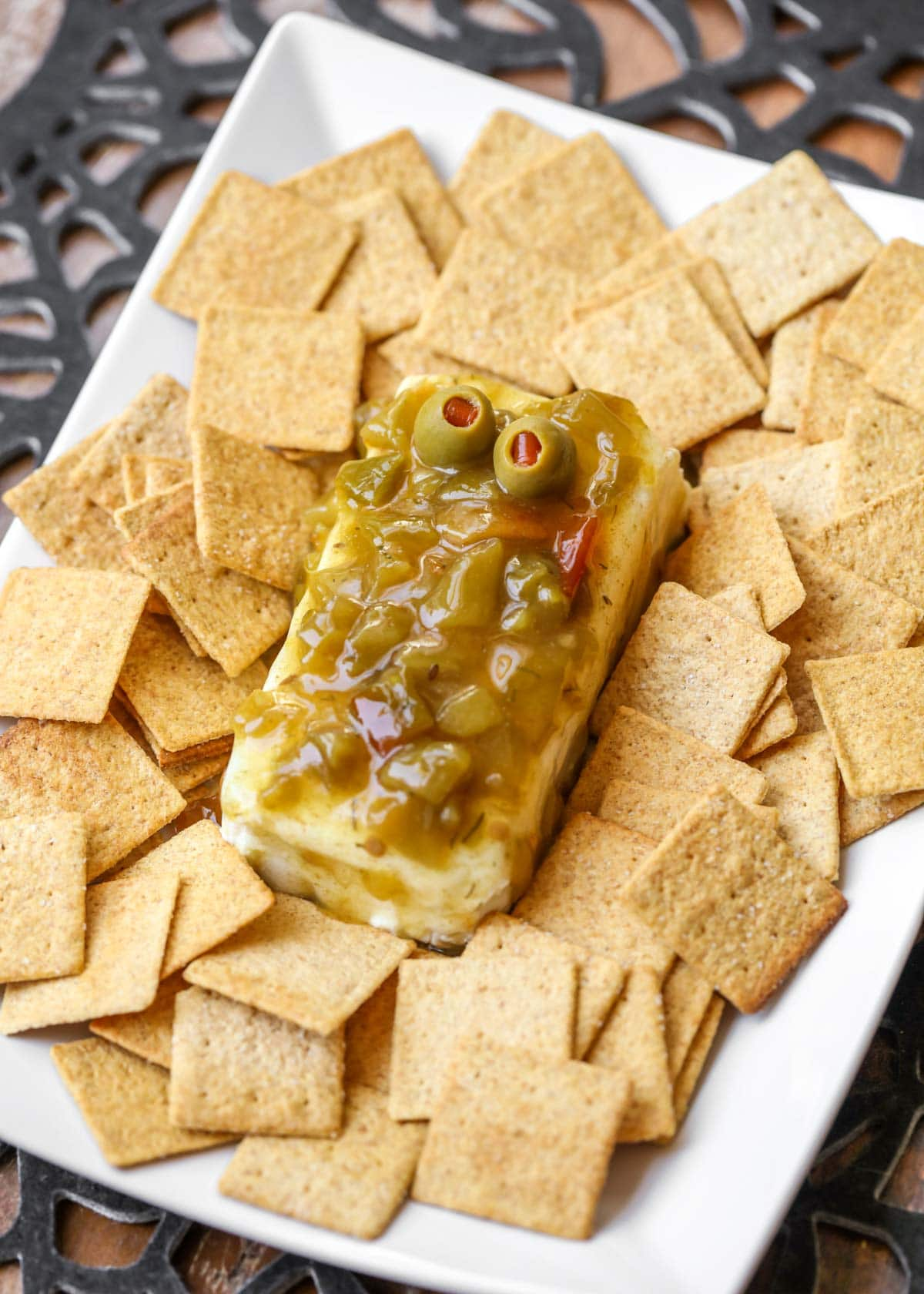 Green chili cream cheese dip with green olives for eyes