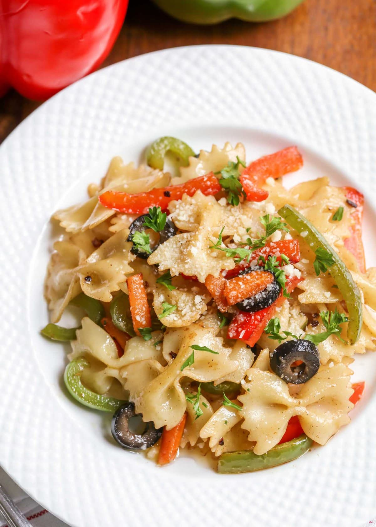 Garlic Butter Pasta recipe with peppers and olives on a white dish