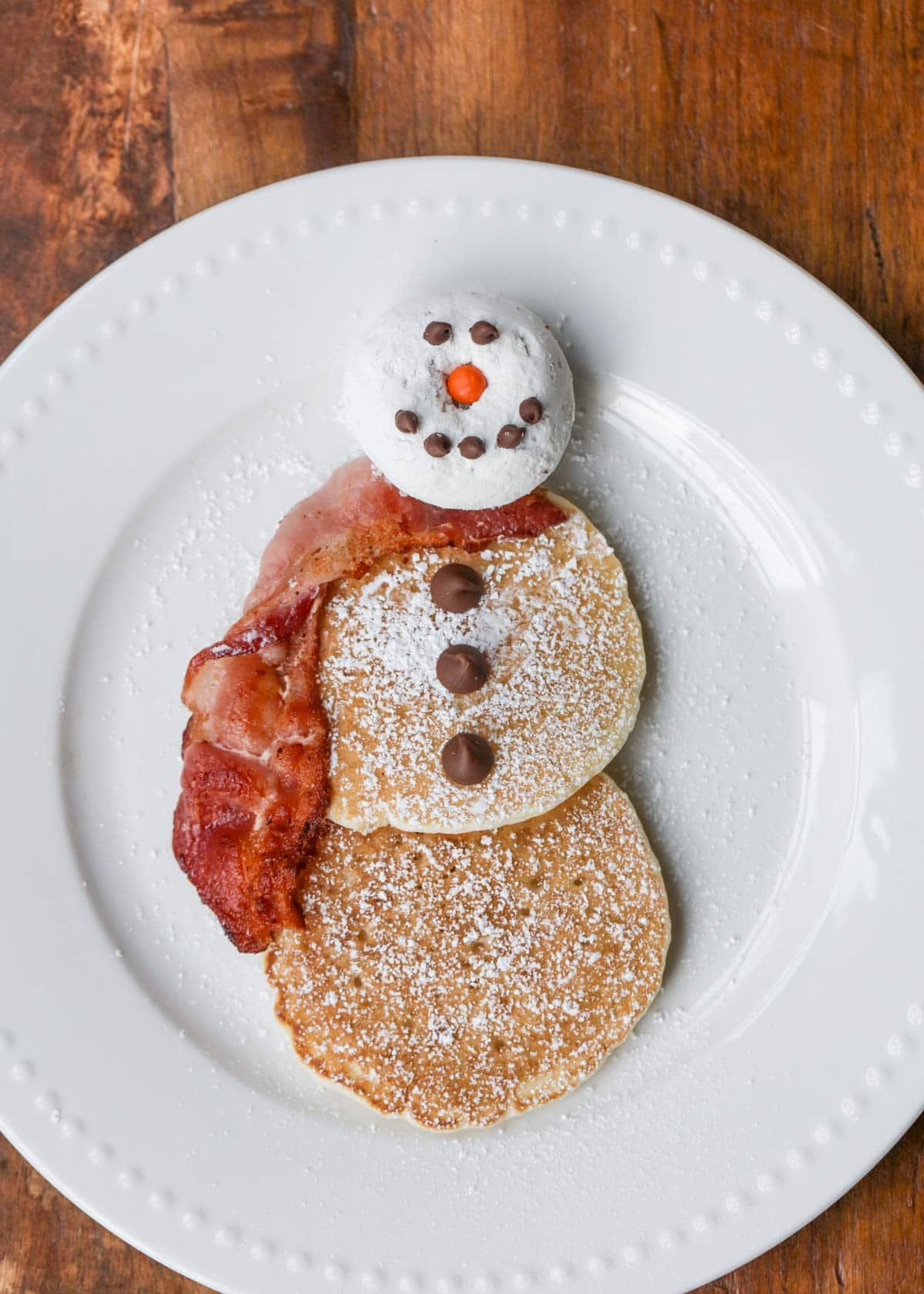 Donut head snowman Christmas pancakes served on a white plate.
