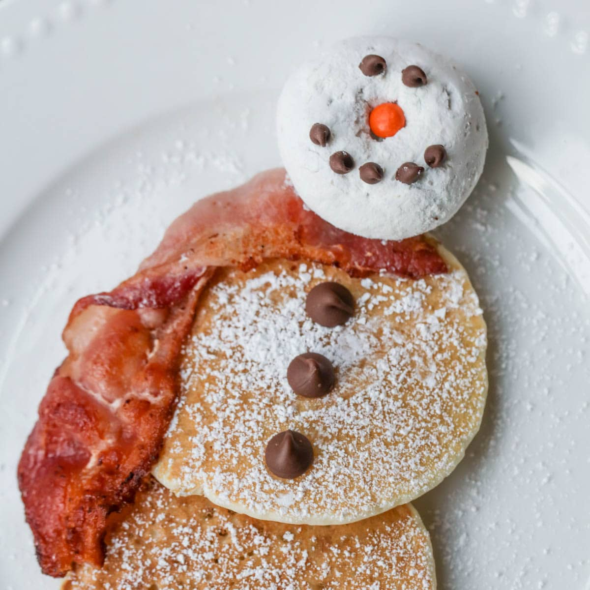 Christmas snowman pancakes plated and decorated with chocolate chips.