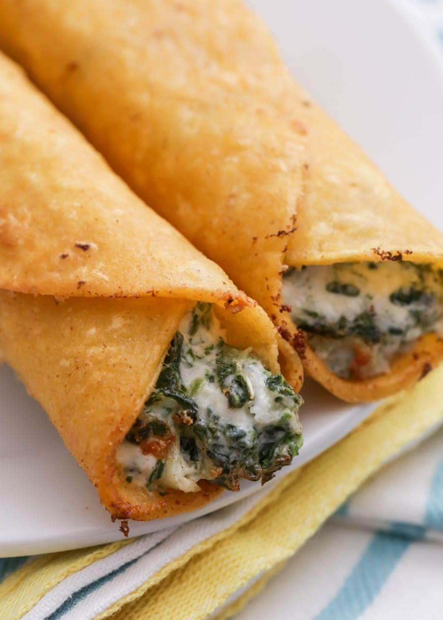 Cheesy Spinach and Artichoke Taquitos fried and served on a white plate