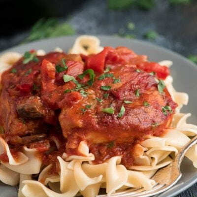 Chicken cacciatore on grey plate served over pasta