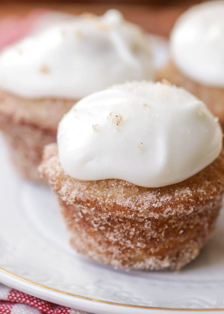 Mini Frosted Cinnamon Donut Muffins - mini donut muffins, rolled in cinnamon sugar, and topped with a DELICIOUS cream cheese frosting. It's hard not to eat the whole batch!!