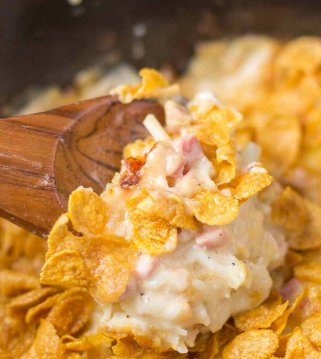 cheesy crockpot hashbrown casserole with corn flakes on wooden spoon