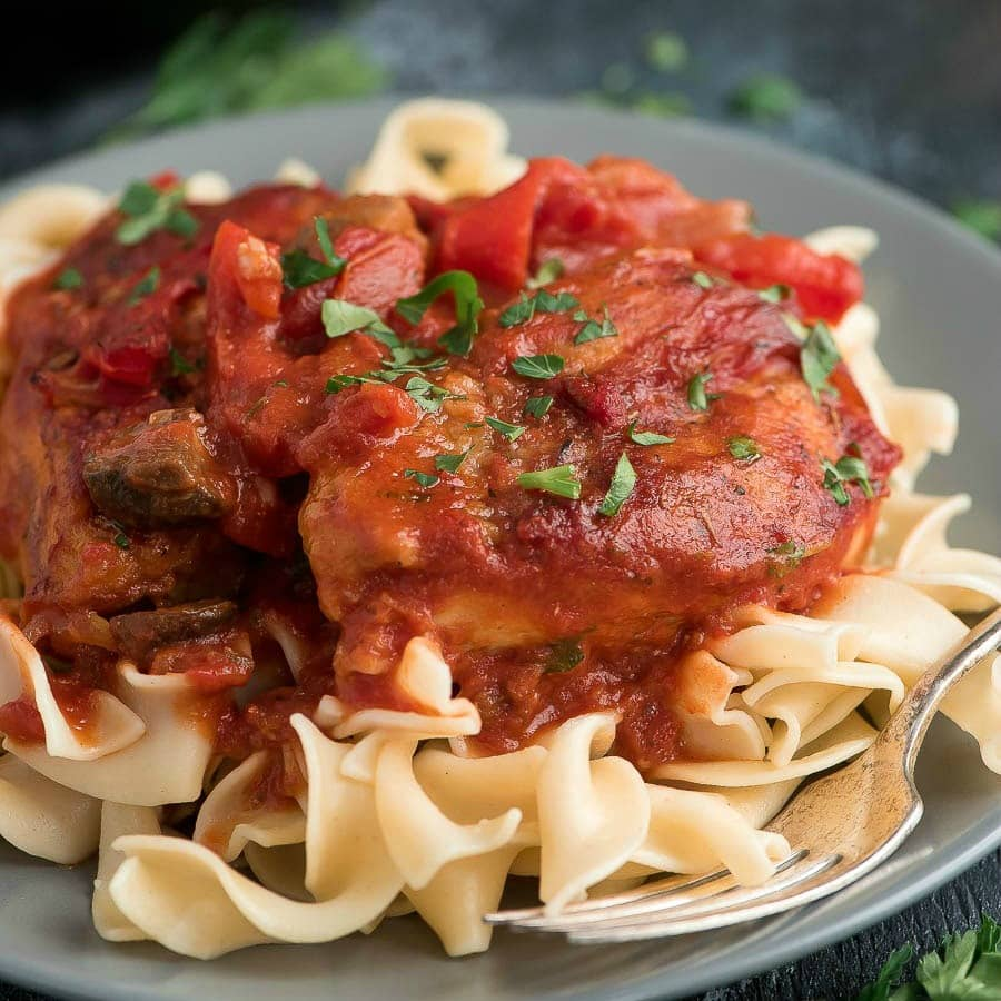 Finished Chicken Cacciatore served over pasta on grey plate