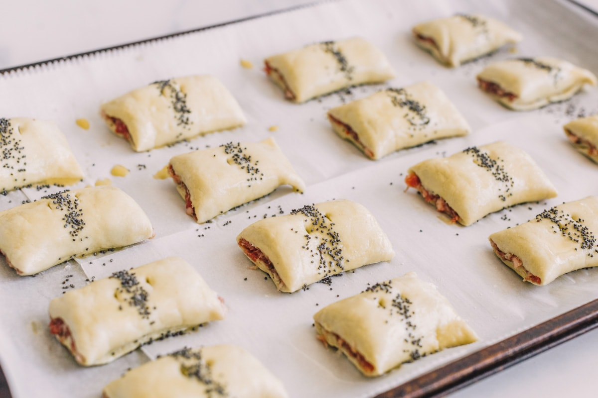 Sausage puff pastry rolls on a baking sheet