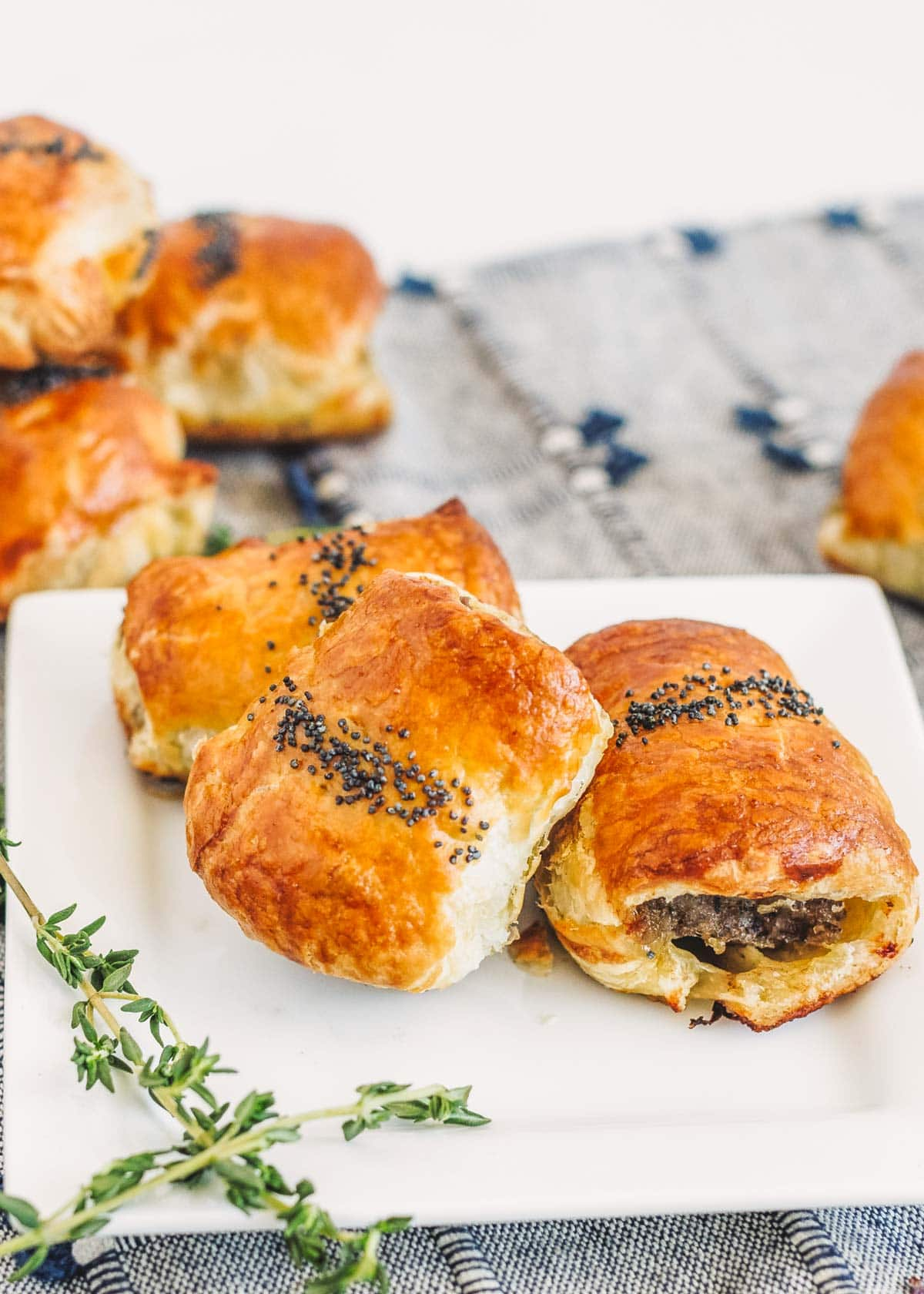 Breakfast sausage rolls stacked on a white plate
