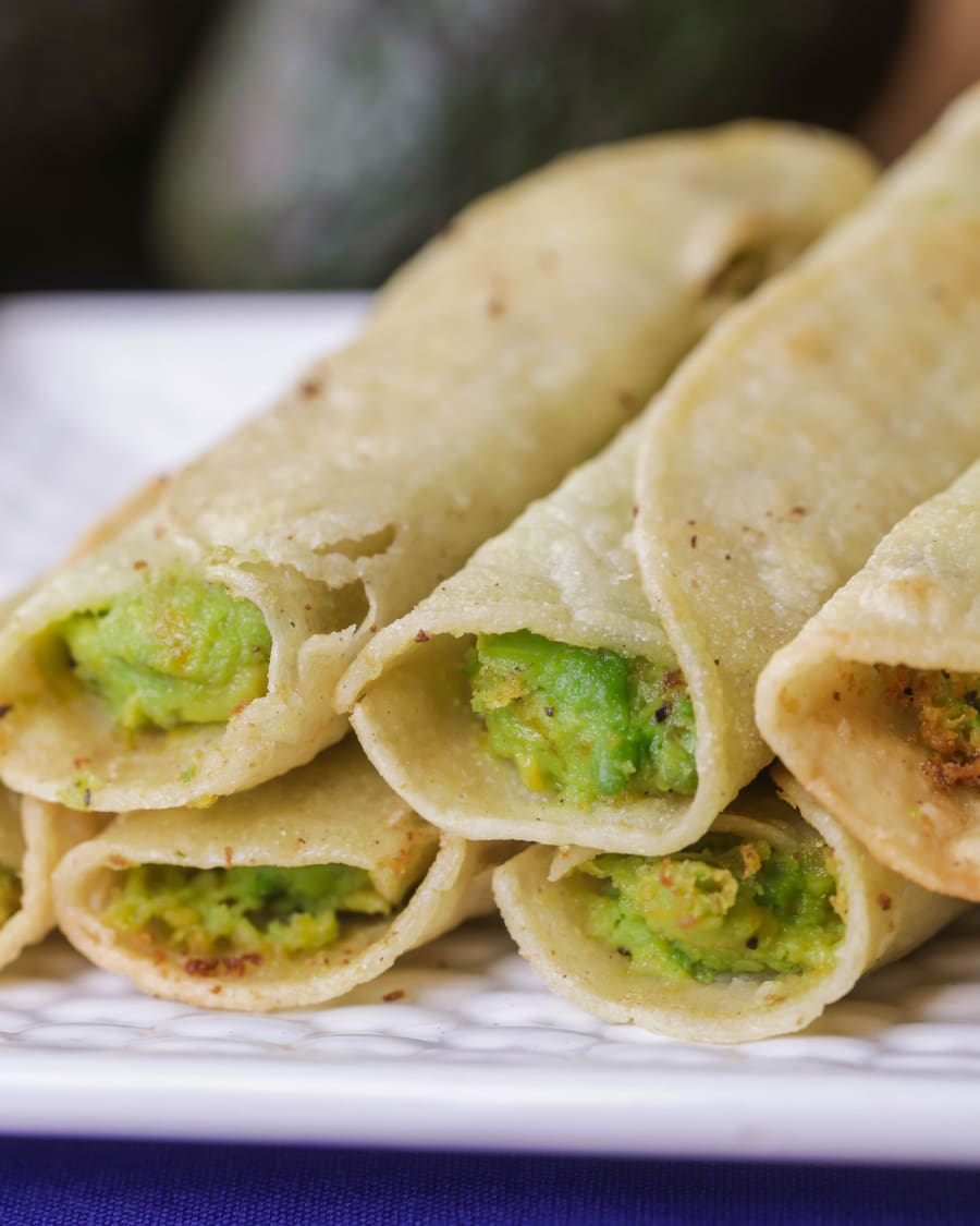 Avocado Taquitos fried and stacked on a white plate