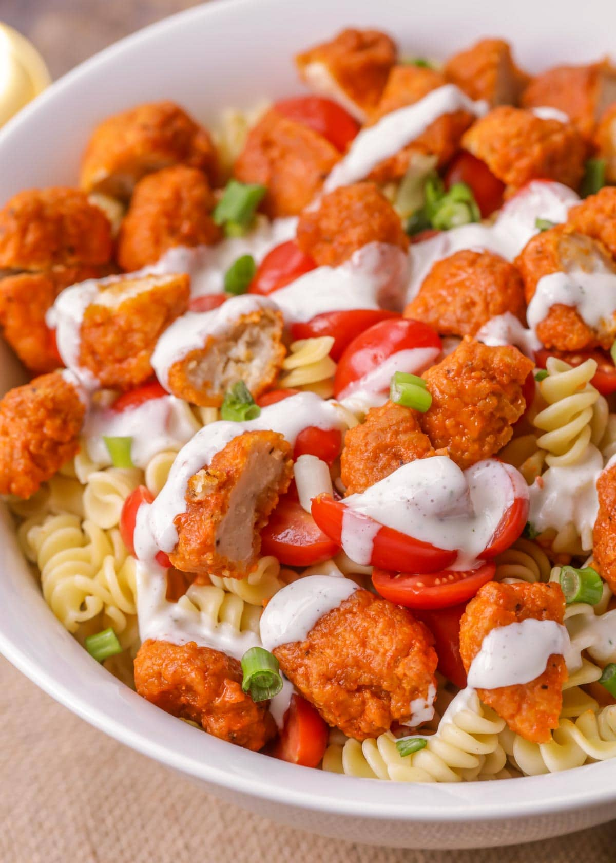 Buffalo chicken pasta salad drizzled with dressing, served in a white bowl.