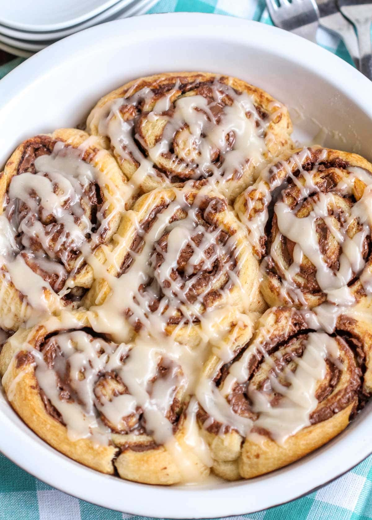 Nutella cinnamon rolls in a round baking dish with glaze drizzled on top