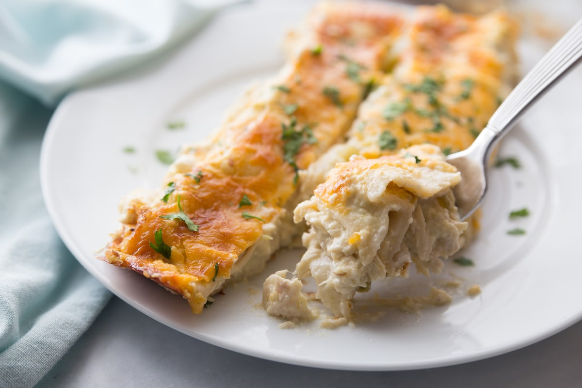 Cream cheese chicken enchiladas on white plate