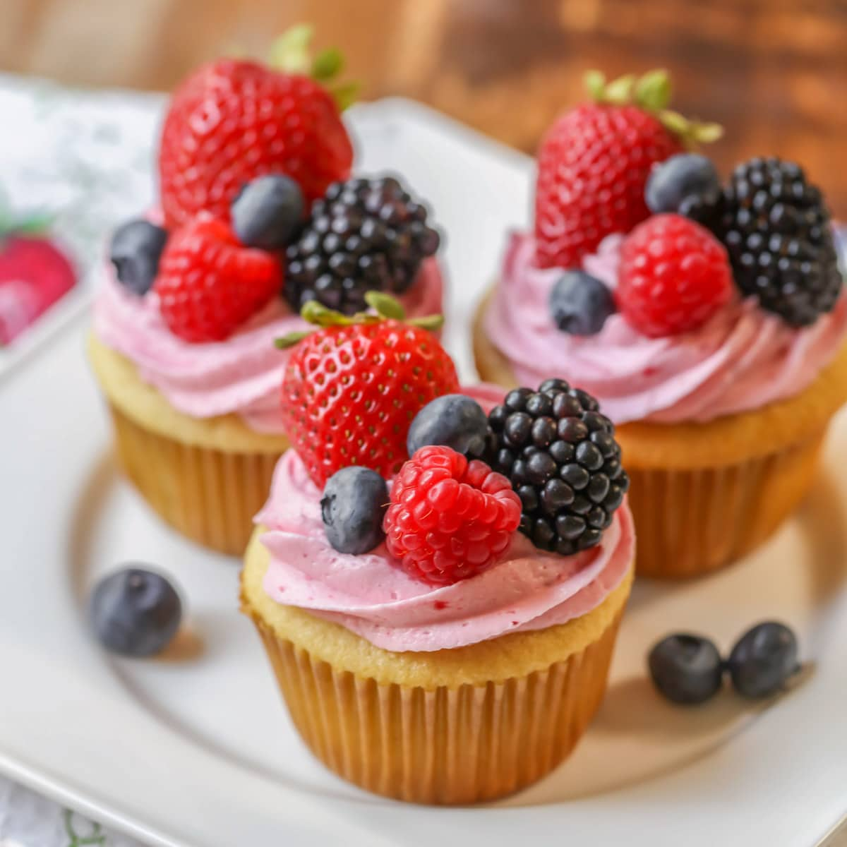 Berry buttercream frosting on top of cupcakes with fresh berries