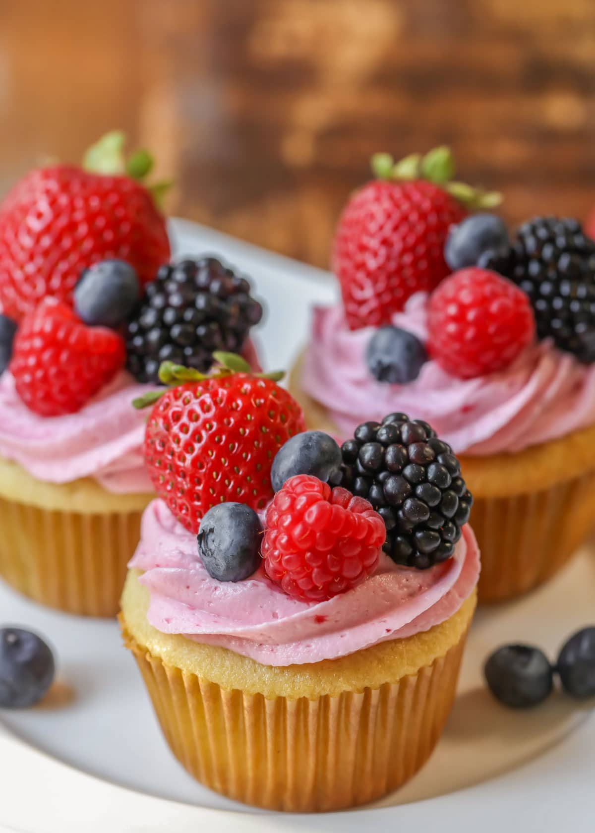 Cupcakes topped with berry frosting and fresh berries