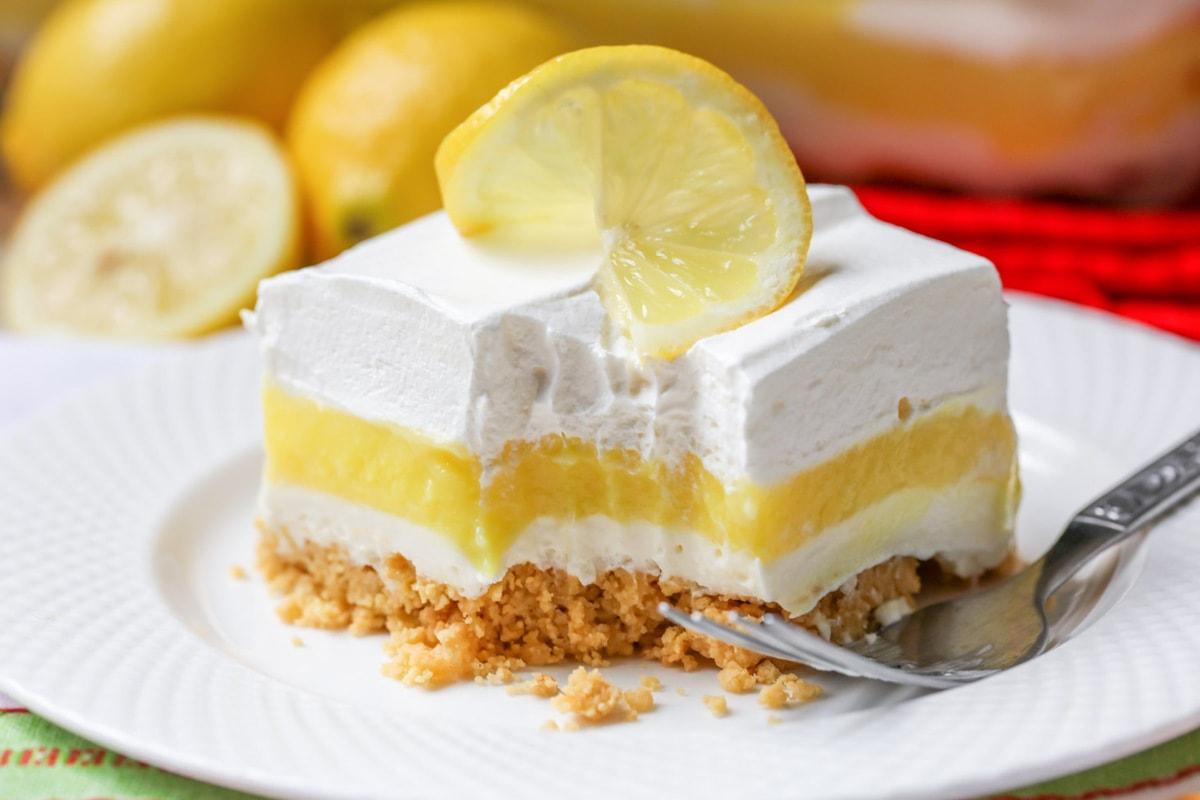 Lemon Lush Lasagna on a white plate with a bite taken out