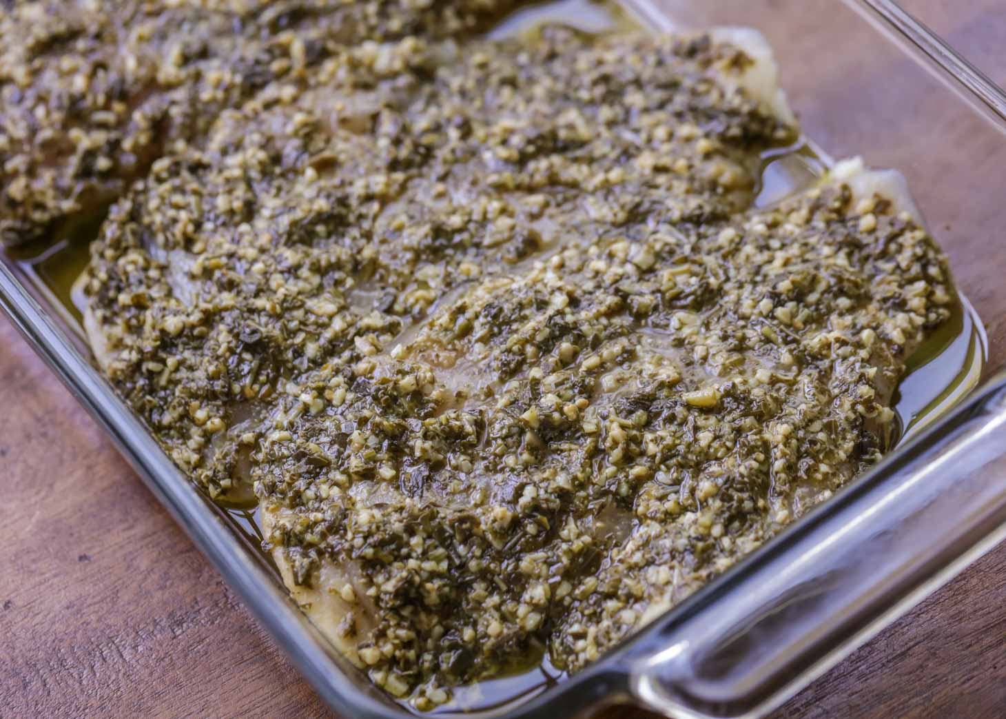 chicken breasts covered with basil pesto in a baking dish