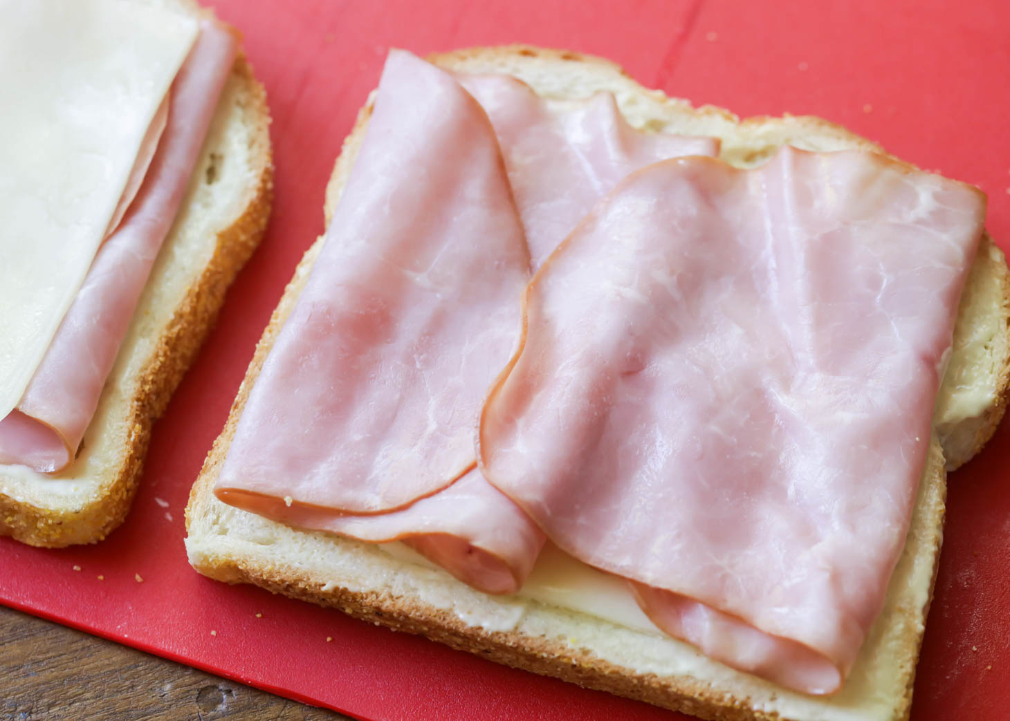Layering ham and cheese on slices of bread to make Croque Monsieur recipe