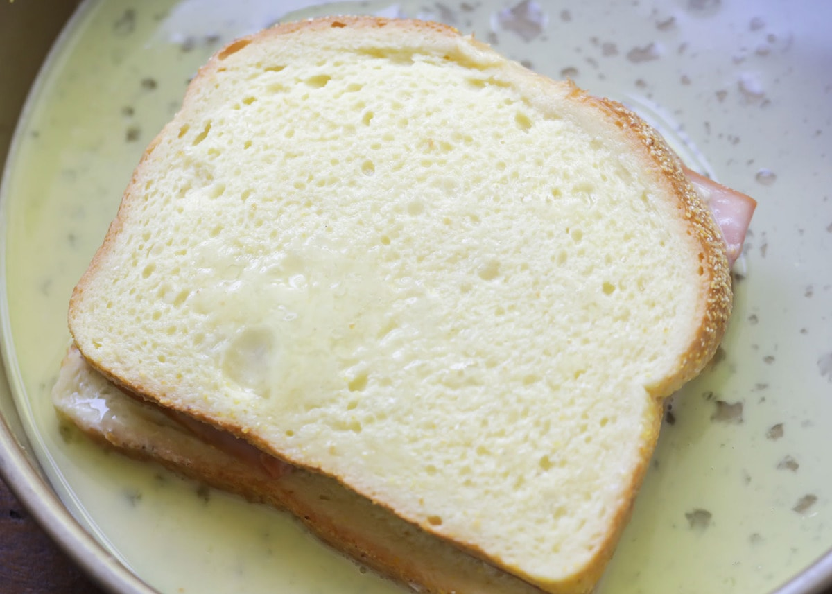 Dipping Croque Monsieur sandwich in egg mixture