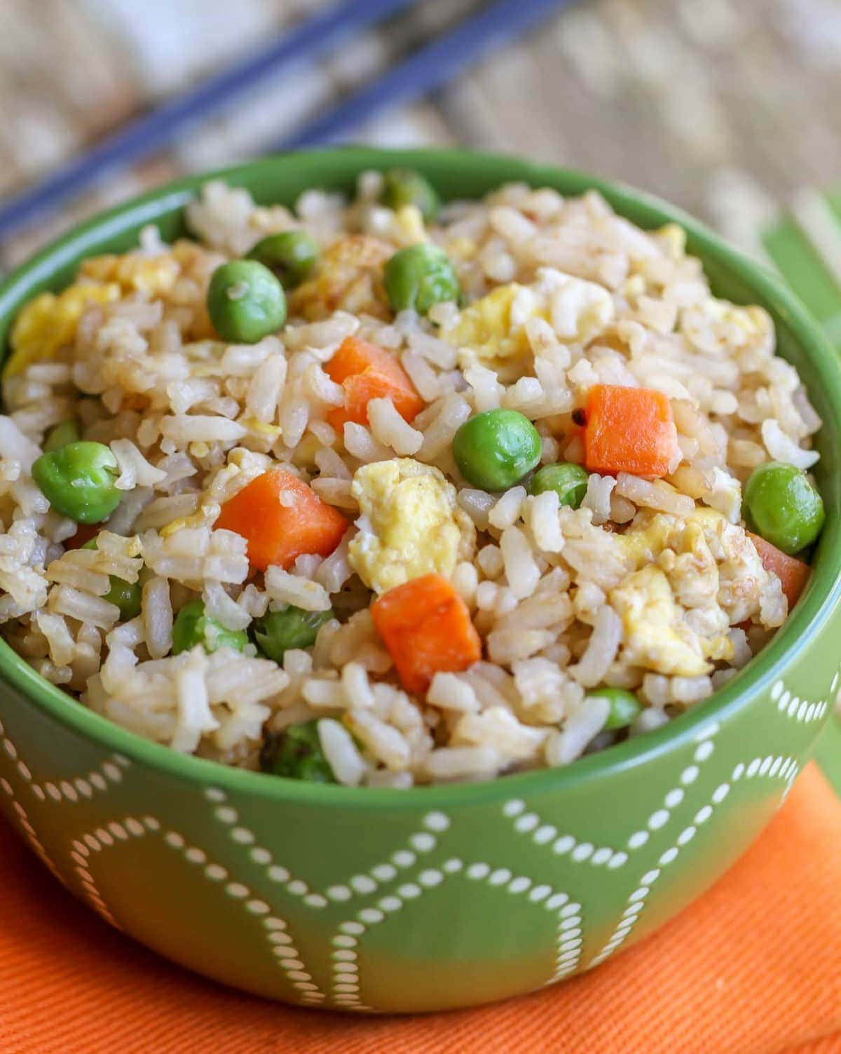 Fried rice with peas, carrots and eggs in a green bowl