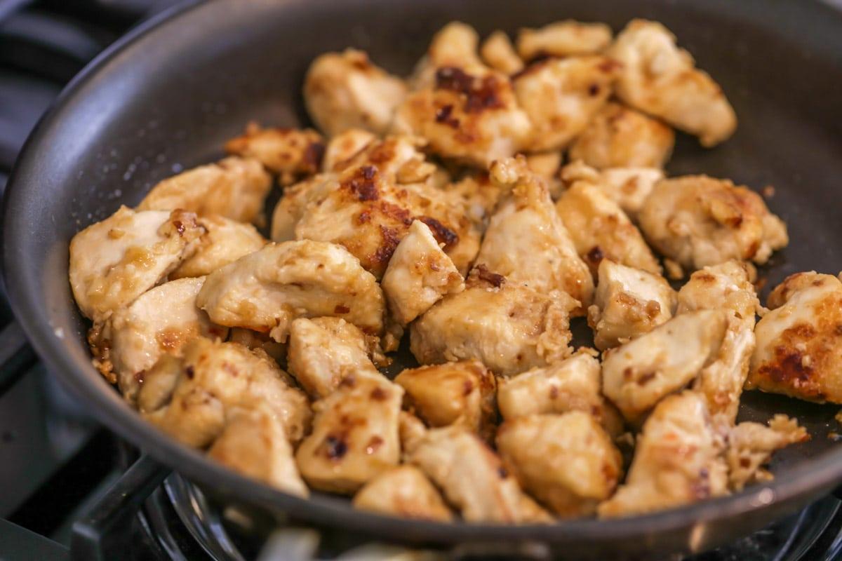 Orange chicken cooking in a skillet