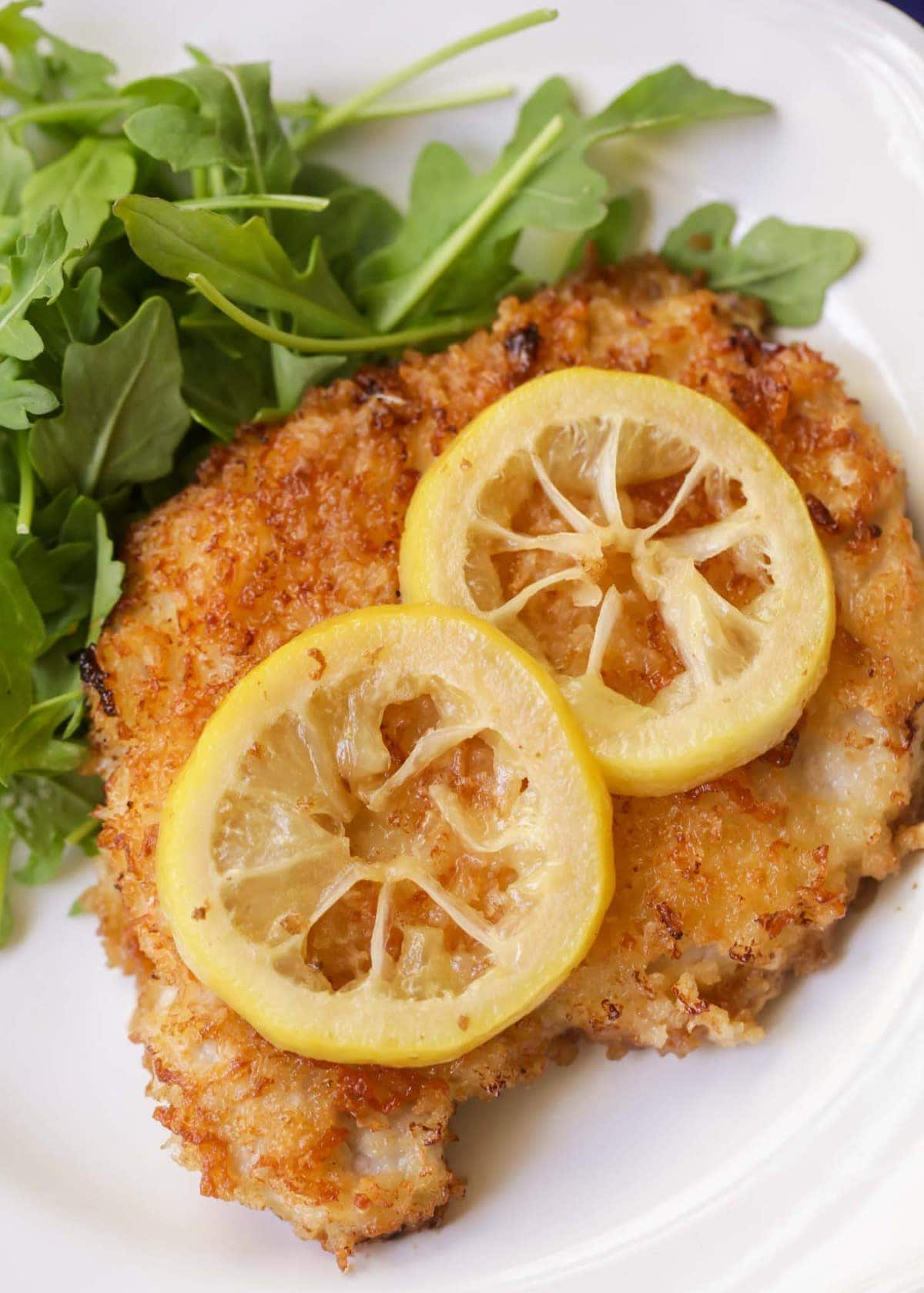 Pan fried pork chops with lemon on a plate
