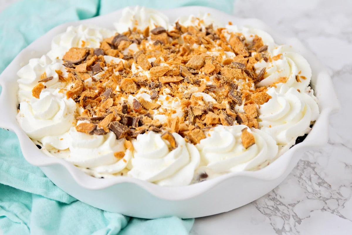 No Bake Butterfinger Pie with whipped cream and crushed butterfinger topping