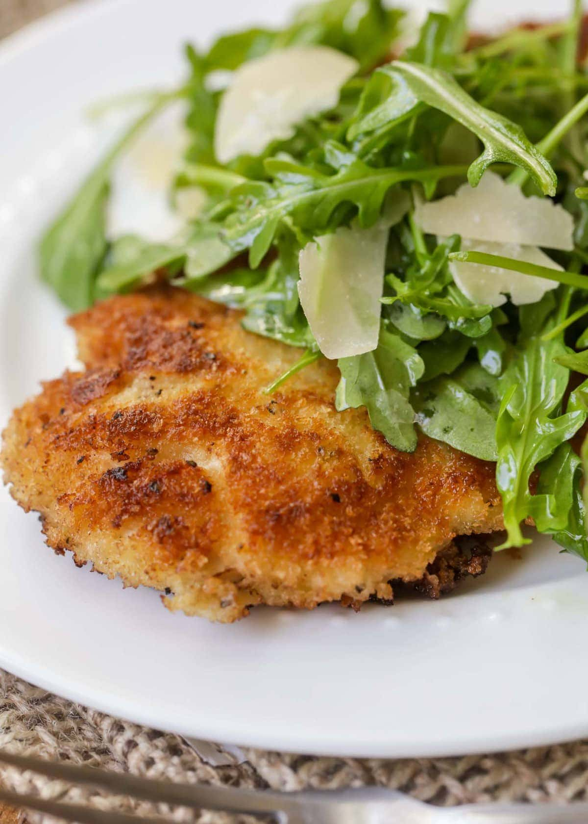 Fried chicken breast with arugula and shaved Parmesan cheese