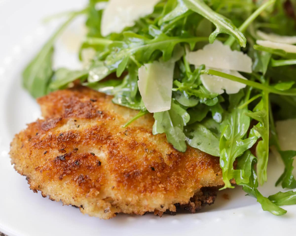 Crispy fried chicken breast recipe topped with arugula