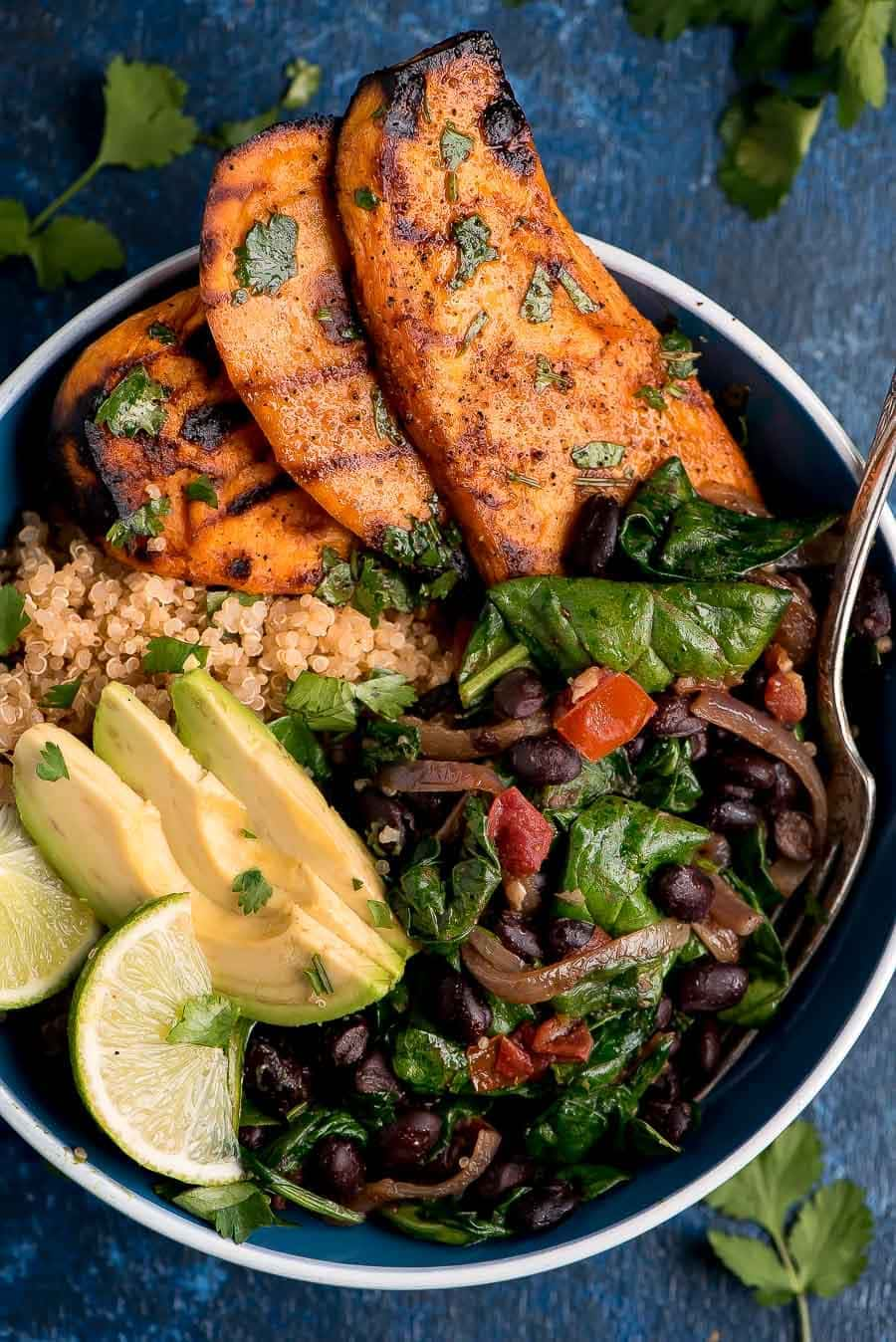 Spinach and Sweet Potato Quinoa Bowl topped with avocado and cilantro