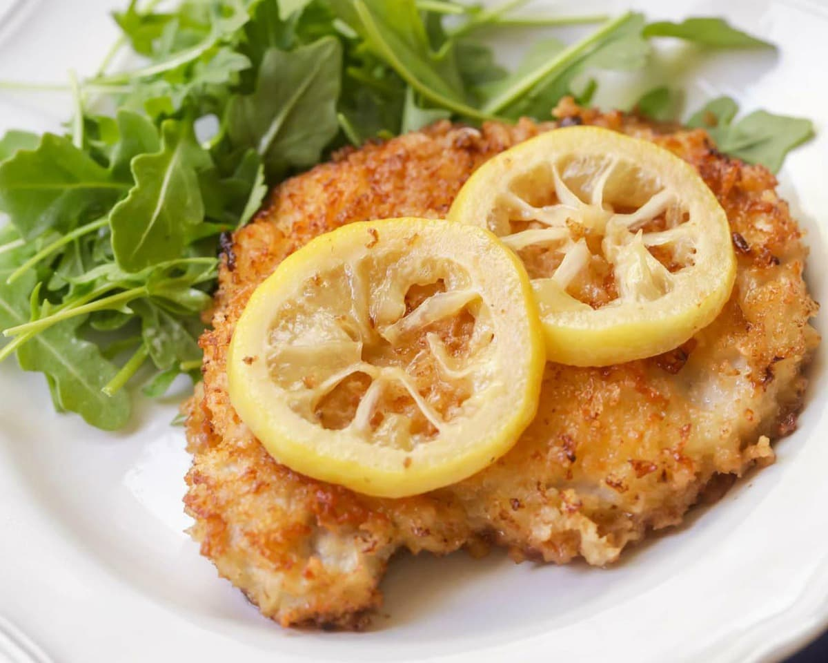 Fried Pork Chops over arugula topped with lemon slices