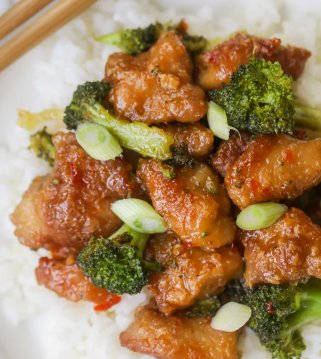 general tso chicken served over white rice and plate with chopsticks