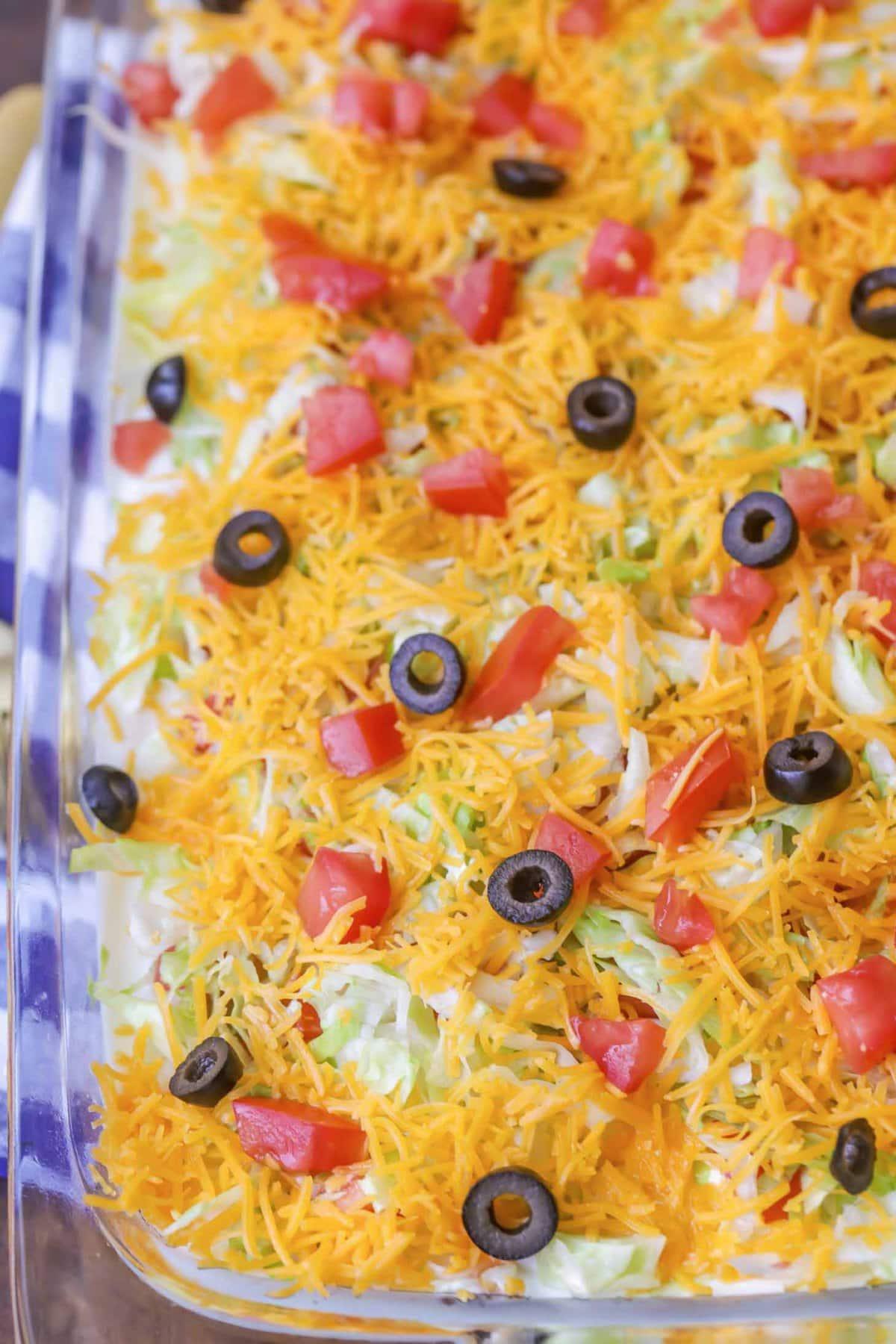Taco Bake Recipe topped with shredded cheese, tomatoes, and olives