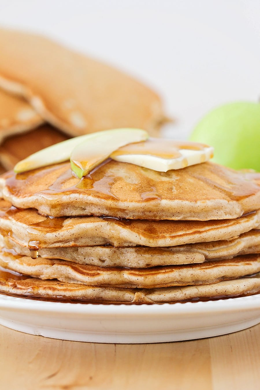 stack of apple cinnamon pancakes on a white plate