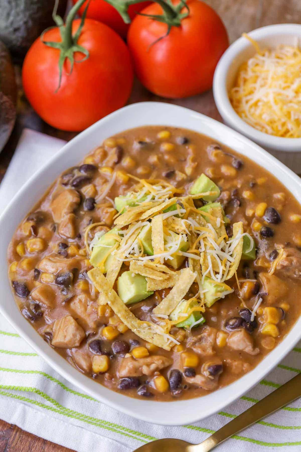A delicious and flavorful Chicken Chili filled with beans, corn, enchilada sauce, spices and topped with tortilla strips, cheese and avocados. Everyone loves this recipe!