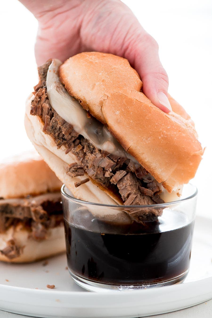 This French Dip Sandwich recipe includes hearty beef, melted provolone cheese, on a buttered toasted bun, and dipped in au jus.