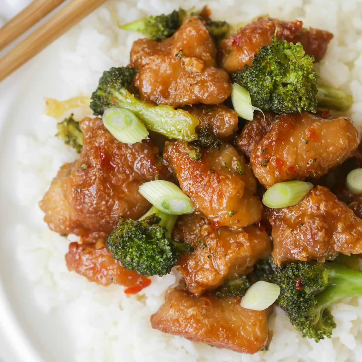 General Tso chicken with broccoli served over white rice on white plate