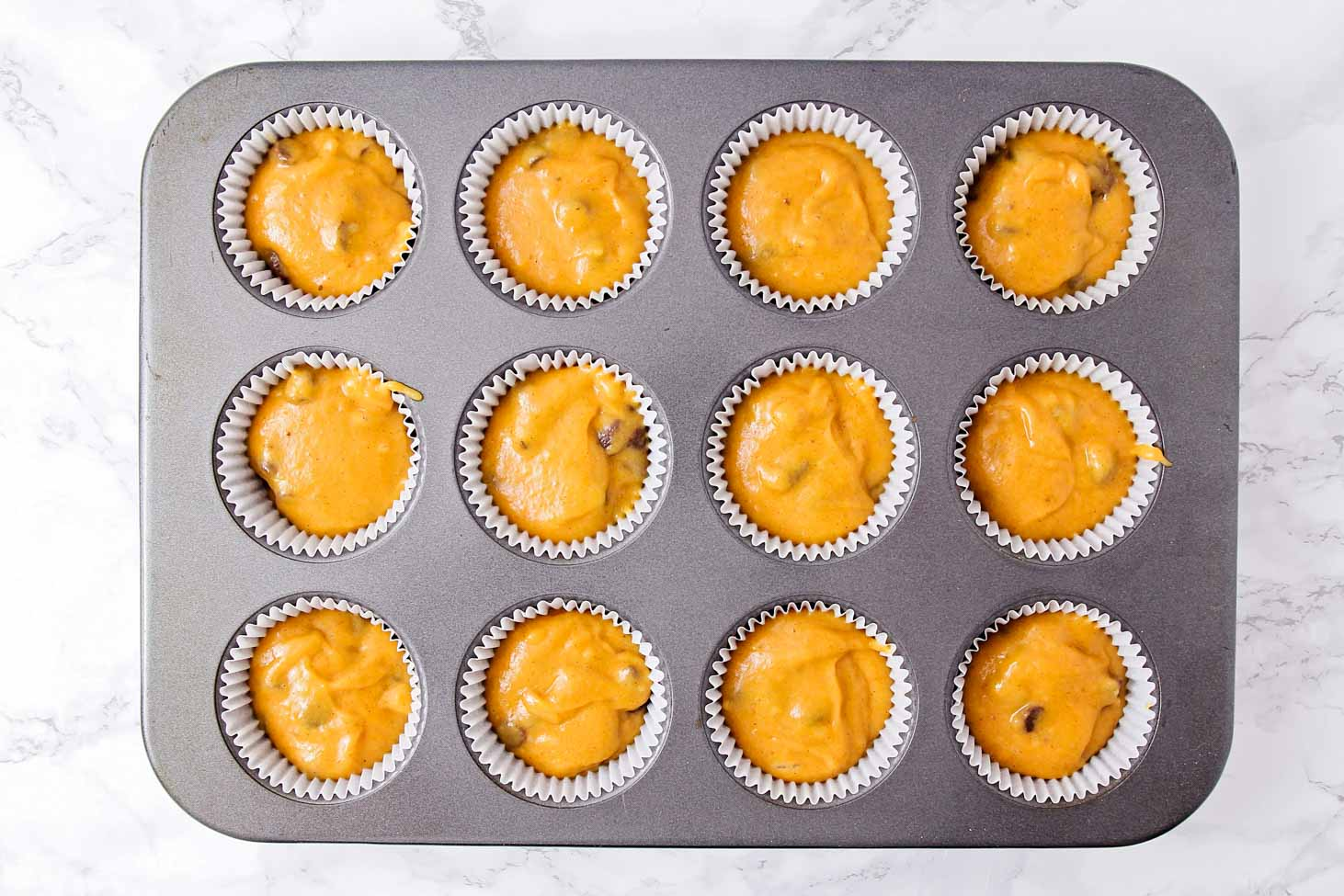 chocolate chip pumpkin muffin batter in muffin tin