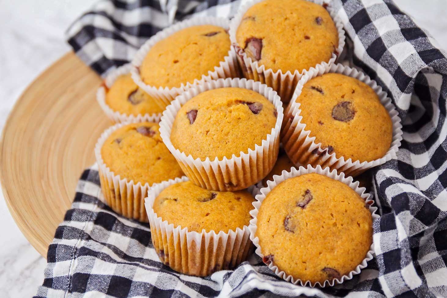 Pumpkin chocolate chip muffins stacked on a dish towel