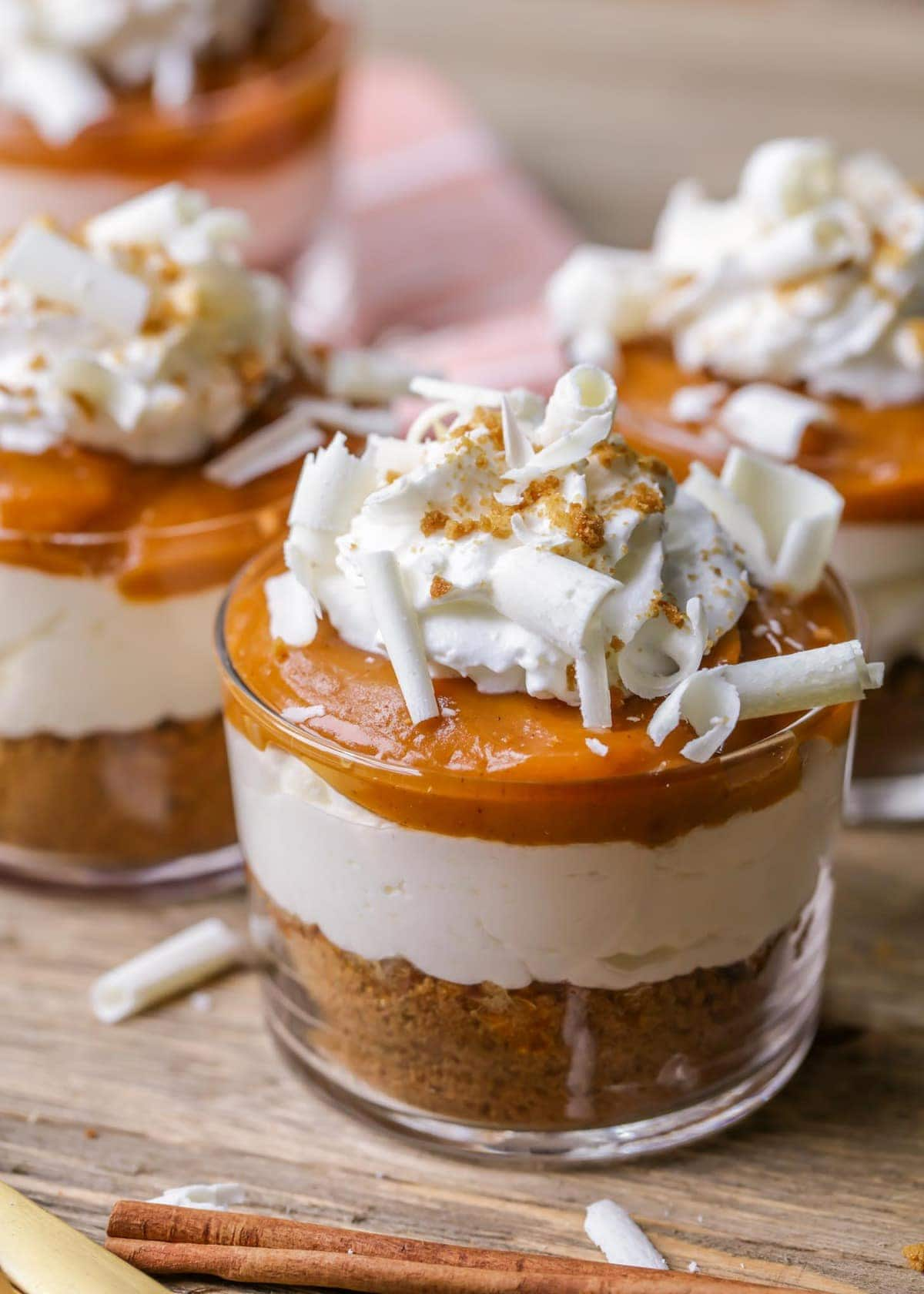 Pumpkin Pudding Parfaits - a ginger snap base, cream cheese layer, pumpkin pudding layer and topped with whipped cream, crumbs and white chocolate curls!