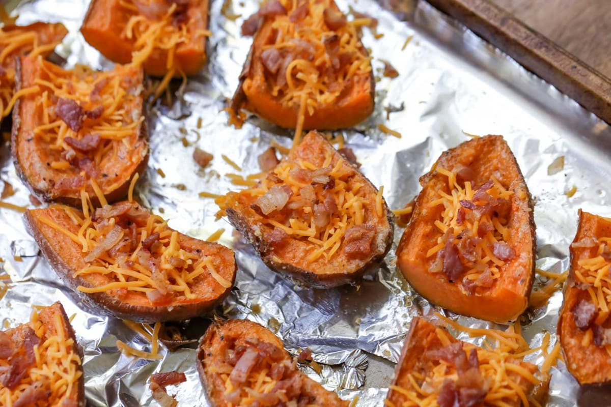 Sweet Potato Skins - a delicious appetizer with a buttery Parmesan crusted glaze and toped with bacon and chives.