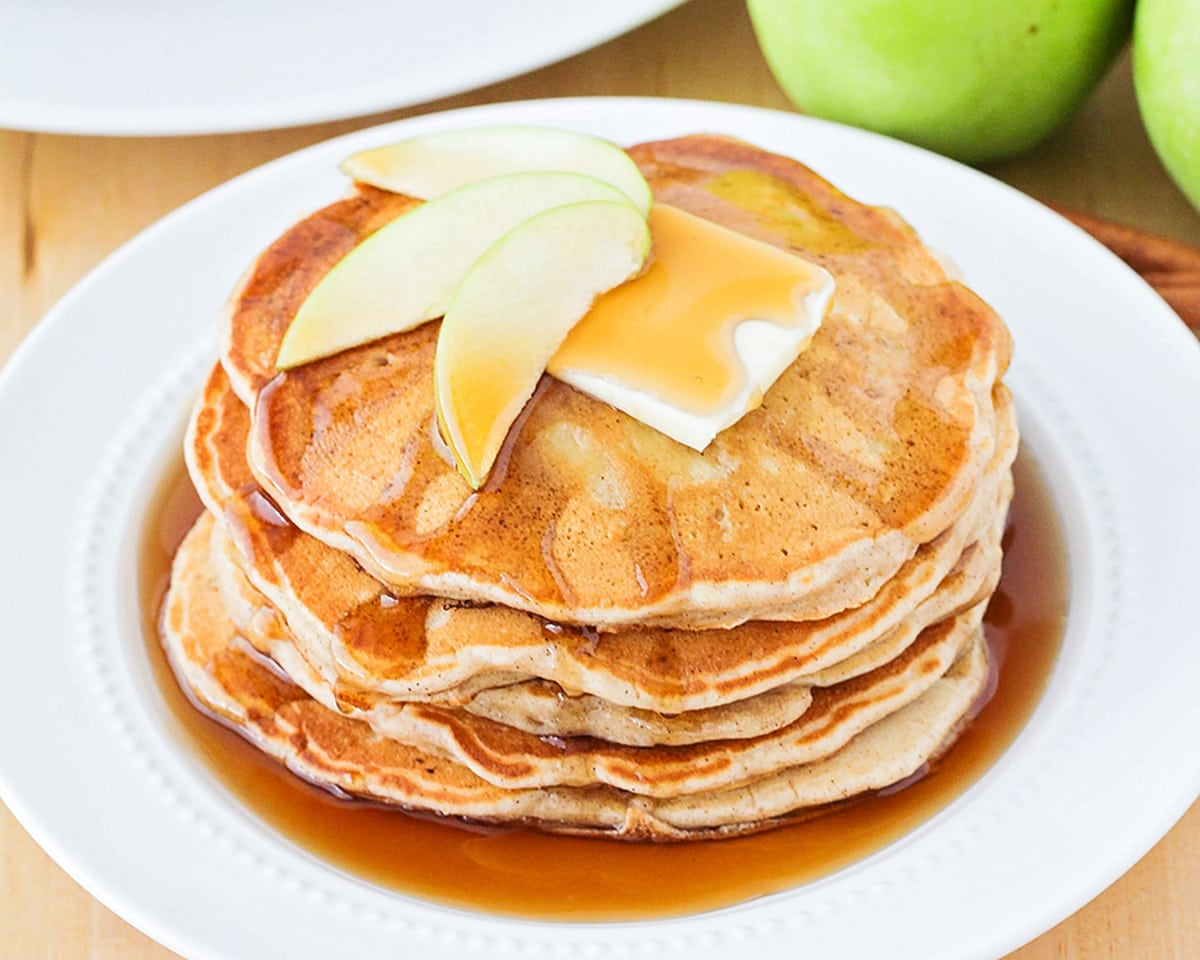 Apple Pancakes topped with apple slices and butter on a white plate