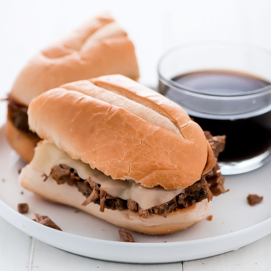 French dip sandwich cut in half and served with au jus