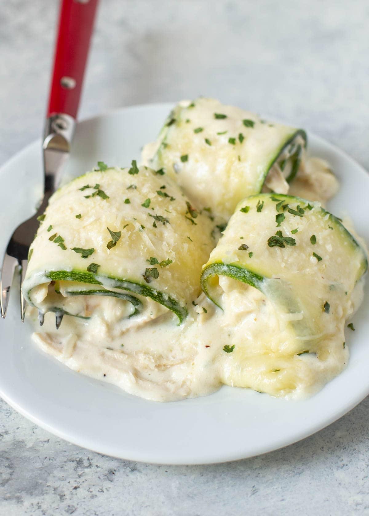 zucchini chicken alfredo roll ups on a white plate