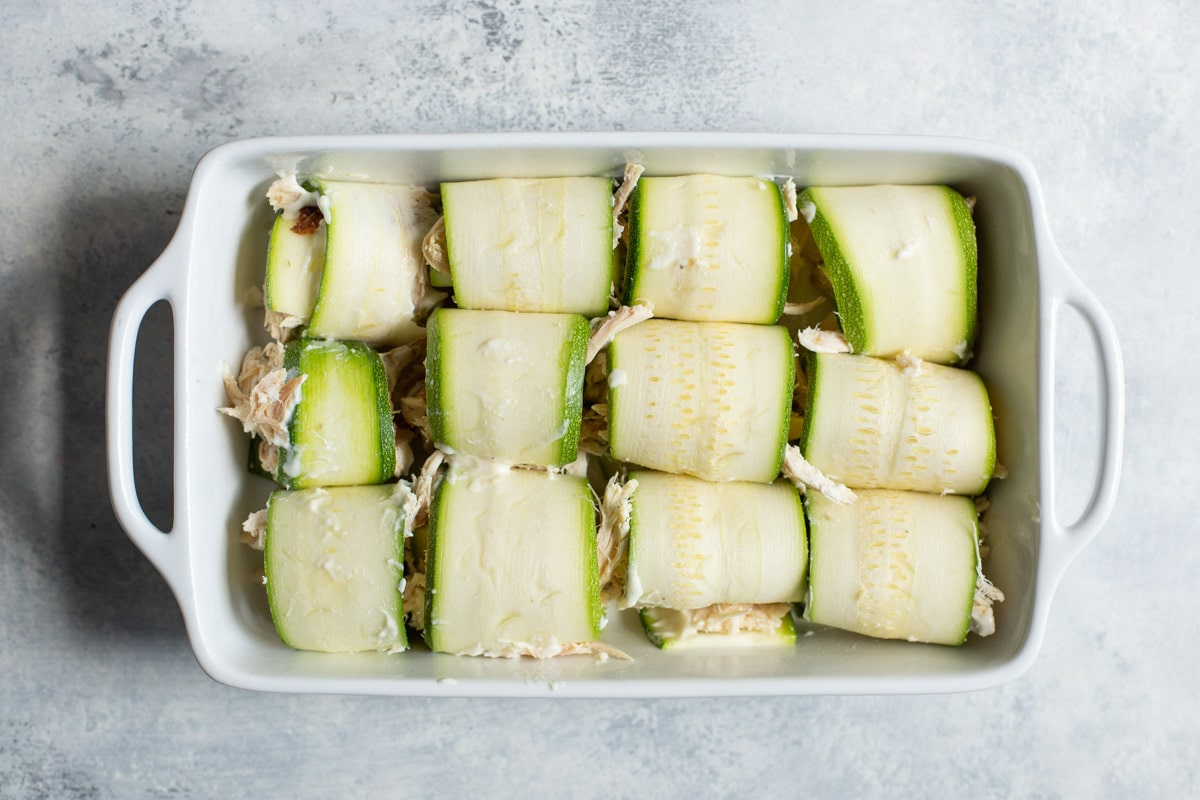 zucchini wrapped chicken in a white baking dish